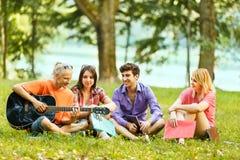 groupe d'étudiants avec une guitare se reposant en parc Photos libres de droits