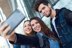 Groupe d'étudiants ayant l'amusement avec des smartphones après classe Photographie stock