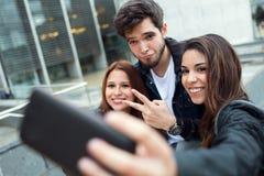 Groupe d'étudiants ayant l'amusement avec des smartphones après classe Image stock