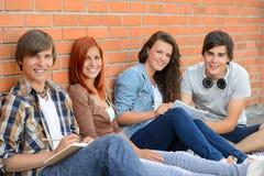 Groupe d'étudiants d'amis s'asseyant dans la rangée Photographie stock