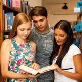 Groupe d'étudiants dans des livres de lecture de bibliothèque - groupe de travail Image libre de droits