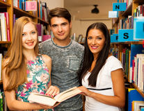 Groupe d'étudiants dans des livres de lecture de bibliothèque - groupe de travail Photos stock
