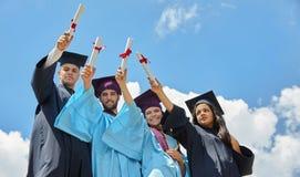 Groupe d'étudiants dans des robes et des chapeaux d'obtention du diplôme Images stock