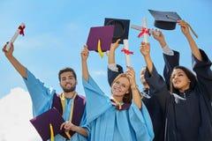 Groupe d'étudiants dans des robes et des chapeaux d'obtention du diplôme Photographie stock