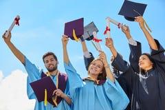 Groupe d'étudiants dans des robes et des chapeaux d'obtention du diplôme Image libre de droits