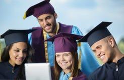 Groupe d'étudiants dans des robes et des chapeaux d'obtention du diplôme Photo stock