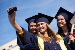 Groupe d'étudiants dans les diplômés faisant le selfie Image libre de droits