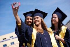 Groupe d'étudiants dans les diplômés faisant le selfie Photo libre de droits