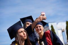 Groupe d'étudiants dans les diplômés faisant le selfie Images libres de droits