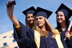 Groupe d'étudiants dans les diplômés faisant le selfie Images stock