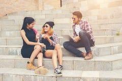 Groupe d'étudiants de hippie s'asseyant sur parler et rel d'un escalier Photographie stock