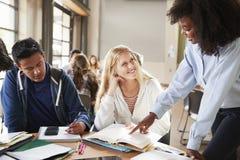 Groupe d'étudiants de lycée avec le professeur féminin Working At Desk image libre de droits