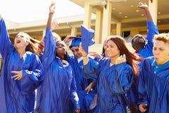 Groupe d'étudiants de lycée célébrant l'obtention du diplôme Images stock