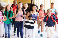 Groupe d'étudiants de lycée courant le long du couloir photos stock