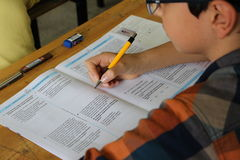 Groupe d'étudiants de lycée passant un examen dans la salle de classe images libres de droits