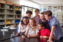 Groupe d'étudiants de lycée regardant le message au téléphone portable dans la salle de classe photographie stock