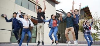 Groupe d'étudiants de lycée sautant en air à l'extérieur des bâtiments d'université photos stock