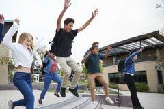Groupe d'étudiants de lycée sautant en air à l'extérieur des bâtiments d'université image stock