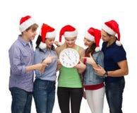 Groupe d'étudiants de sourire avec l'horloge montrant 12 Photographie stock libre de droits