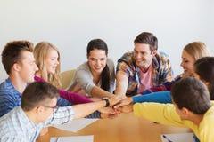 Groupe d'étudiants de sourire avec la main sur le dessus Images stock