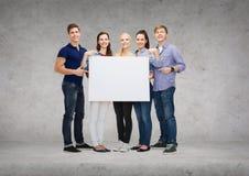 Groupe d'étudiants de sourire avec le conseil vide blanc Photo stock