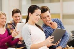 Groupe d'étudiants de sourire avec le PC de comprimé Photos stock