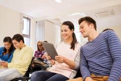 Groupe d'étudiants de sourire avec le PC de comprimé Photo stock