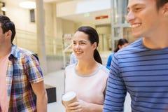 Groupe d'étudiants de sourire avec les tasses de café de papier Photo stock
