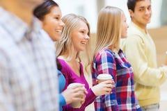 Groupe d'étudiants de sourire avec les tasses de café de papier Images libres de droits