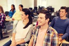 Groupe d'étudiants de sourire dans la salle de conférences Photos stock