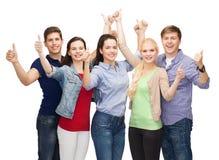 Groupe d'étudiants de sourire montrant des pouces  Photographie stock libre de droits