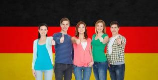 Groupe d'étudiants de sourire montrant des pouces Images stock