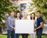Groupe d'étudiants debout avec le conseil blanc vide Photo stock