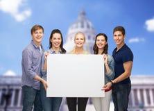 Groupe d'étudiants debout avec le conseil blanc vide Photographie stock