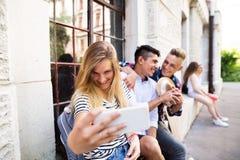 Groupe d'étudiants devant l'université prenant le selfie Image libre de droits