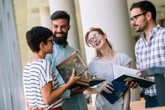 Groupe d'étudiants discutant à la bibliothèque universitaire Images stock
