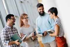 Groupe d'étudiants discutant à la bibliothèque universitaire Photo stock
