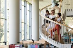 Groupe d'étudiants discutant à la bibliothèque universitaire Photo libre de droits