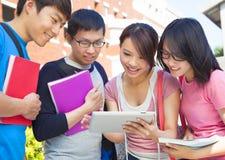 Groupe d'étudiants discutant le travail à l'aide du comprimé Photographie stock libre de droits
