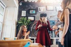Groupe d'étudiants distribuant ensemble les films de observation de fille dans des lunettes de la réalité virtuelle 3d, attente d Image stock