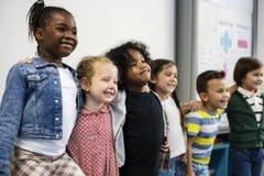 Groupe d'étudiants divers de jardin d'enfants se tenant ensemble dans les clas photographie stock libre de droits