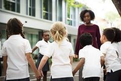Groupe d'étudiants divers de jardin d'enfants se tenant tenants des mains sur Photos stock