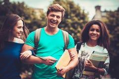 Groupe d'étudiants ethniques multi marchant dans une ville Photos stock