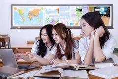 Groupe d'étudiants féminins étudiant dans la classe Image stock