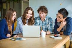 Groupe d'étudiants gais positifs faisant le travail ensemble dans la salle de classe Photographie stock