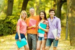 Groupe d'étudiants heureux avec des livres en parc Photos stock