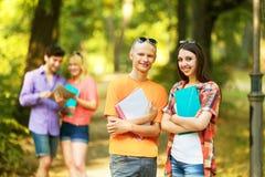 Groupe d'étudiants heureux avec des livres en parc Images libres de droits