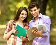 Groupe d'étudiants heureux avec des livres pendant le jour ensoleillé de parc Photo stock