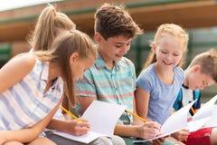 Groupe d'étudiants heureux d'école primaire dehors Image stock