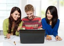 Groupe d'étudiants heureux de diversité étudiant ensemble utilisant l'ordinateur portable Image stock